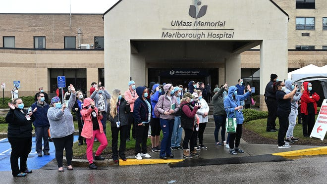 UMass Memorial Marlborough Hospital employees watch as a rolling parade of police and fire personnel thanks them for their work during the coronavirus pandemic in April.