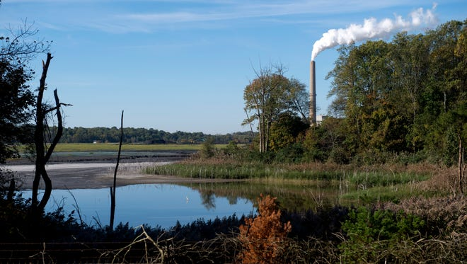 The smokestacks of Vectren's A.B. Brown Generating Station can be seen in the distance behind its coal ash pond in Posey County near Evansville. Vectren has cited the cost of closing the coal ash pond and other environmental updates as reasons for retiring the aging facility. The Indiana Utility Regulatory Commission has rejected Vectren's plan to replace it with a large natural gas-fueled power plant.
