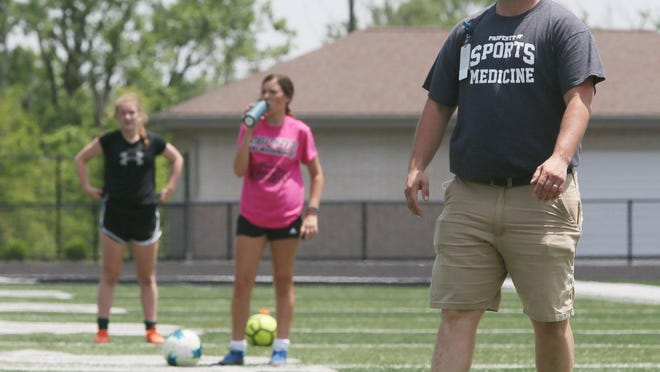 Highland trainer Michael Johnson watches as members of the girls soccer team maintain their distance as they work out at the football stadium at Highland High School on Wednesday, June 19, 2020, in Medina.