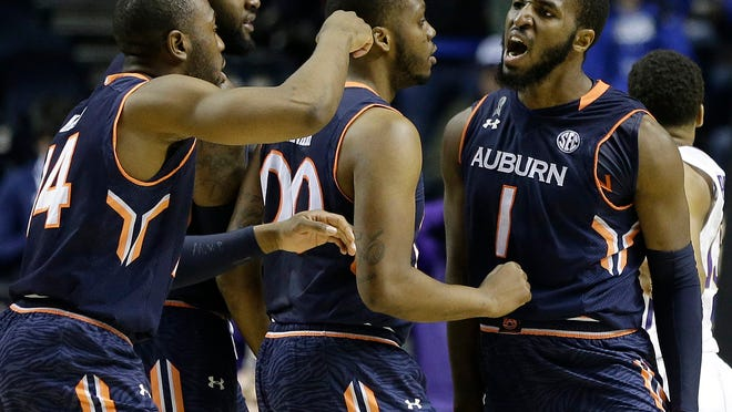 Auburn guard KT Harrell (1) celebrates with team members after he hit a three-point shot during the second half of an NCAA college basketball game in the quarterfinal round of the Southeastern Conference tournament against LSU, Friday, March 13, 2015, in Nashville, Tenn. (AP Photo/Mark Humphrey)