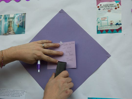 Joel Courtney places a note on a bulletin board reading,