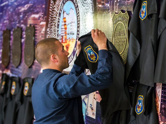 A recruit in the 96th Wilmington Police Academy unveils a plaque Friday honoring Officer Francis X. Tierney, killed in the line of duty in 1915, at the dedication of a memorial wall honoring the city's fallen officers on the first floor of Wilmington Police Department headquarters on Walnut Street.