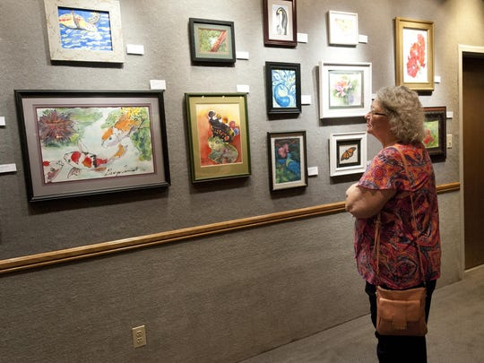 Nancy Quinn looks at paintings on Thursday done by her fellow artists from the Tulare Senior Center. The Tulare Historical Museum is hosting a new exhibit featuring artists from art classes at the Tulare Senior Center. The museum hosted an artists' reception to kick off the exhibit.