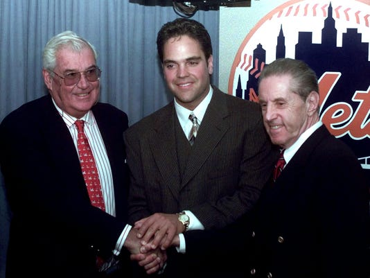 FILE - In this Oct. 26, 1996, file photo, New York Mets catcher Mike Piazza, center, smiles with Mets owners Nelson Doubleday, left, and Fred Wilpon, after the press conference about Piazza's record seven-year $91 million dollar contract with the Mets at New York's Shea Stadium.  Ken Griffey Jr. seems assured of election to the Baseball hall of Fame on the first try Wednesday, Jan. 6, 2016, possibly with a record vote of close to 100 percent. Mike Piazza, Jeff Bagwell and Tim Raines also were strong candidates to gain the 75 percent needed for baseball's highest honor.  (AP Photo/Adam Nadel, File)