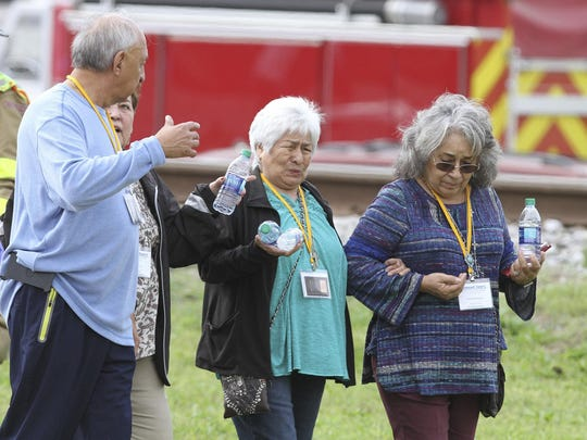 Passengers from a charter bus with minor injures walk to a waiting school bus after their bus was hit by a CSX train at the Main Street crossing in Biloxi, Miss., on Tuesday, March 7, 2017. The bus was carrying 50 people from Austin, Texas, Biloxi Police Chief John Miller said at a news conference. He said authorities believe the bus was stopped on the tracks at the time of the crash, but they don't yet know why.
