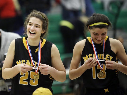 McAuley's Emily Vogelpohl and Sydney Lambert celebrate after winning the district championship Saturday, March 7.