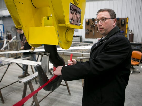 Marshfield Area Chamber of Commerce and Industry executive director Scott Larson ties a ribbon to a hook before the ribbon cutting ceremony for Paget Equipment's expansion in Marshfield in 2015. The hook is part of a new crane system, which was part of the expansion.