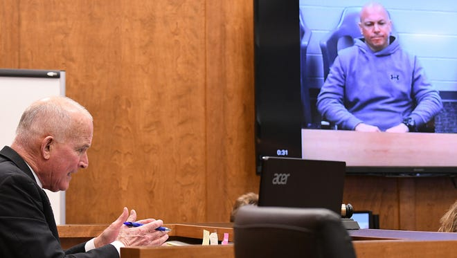 Visiting Judge Richard Reinbold explains the criteria he used to decide moving Larry Evans (pictured on screen) from the Timothy B. Moritz Unit in Columbus to Heartland Behavioral Health Care, a less-restrictive mental health facility in Massillon.