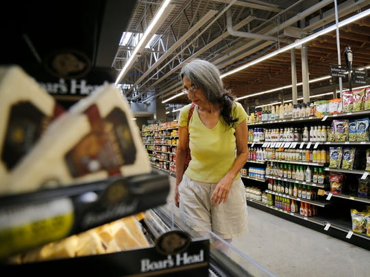 "Self-employed writing teacher Valerie Chronis Bickett, 69, of Clifton, browses the cheese selection at Clifton Market grocery store in the Clifton neighborhood of Cincinnati on Tuesday, Aug. 29, 2017. Chronis Bickett says she shops at Clifton Market because she prefers a store that ""stands for something""."