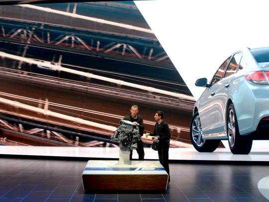 A pair of photographers check out an engine Tuesday, Jan. 12, during the North American International Auto Show at Cobo Hall.