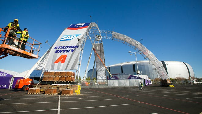 Workers add structures outside of University of Phoenix Stadium in Glendale, Ariz., host of Super Bowl XLIX.