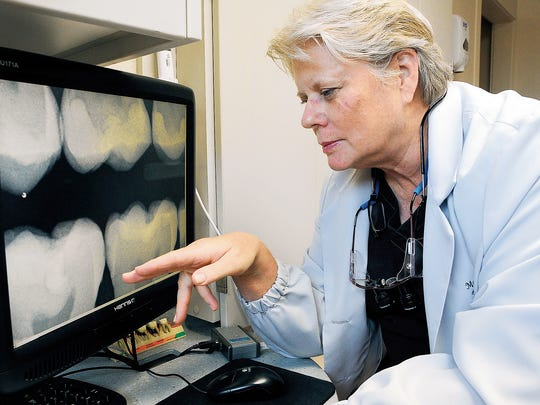 "Dentist Marianne Day looks over a set of digital X-rays at her office. Dentists recommend brushing at least twice a day and more often if your diet is high in simple carbohydrates. ""Think two by two,"" Day said. ""Twice a day, two minutes each time, a day."""