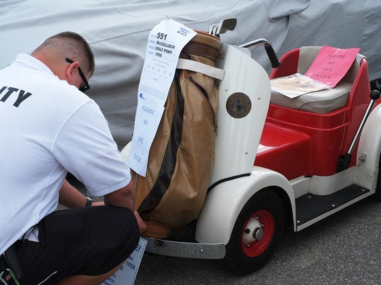 A security guard affixes an information sheet to a 1956 McCulloch Golf Pony during the annual McCormick's Collector Car Auction in Palm Springs Saturday November 22, 2014 .
