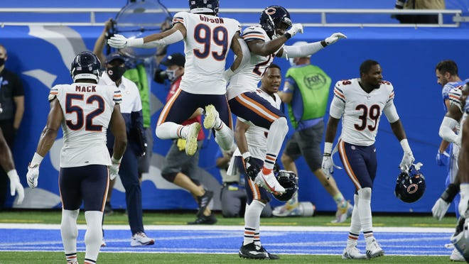 Chicago Bears' Trevis Gipson (99) and  Sherrick McManis (27) celebrate their 27-23 win against the Detroit Lions in Detroit on Sunday.