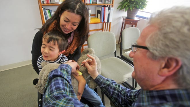 Aurelien Haberkorn, 6, of Harrison, is held by his mother, Veronique, as Dr. Alain Le Guillou administers a polio booster. Le Guillou, a Larchmont pediatrician, believes strongly in sticking to the recommended vaccine schedule.