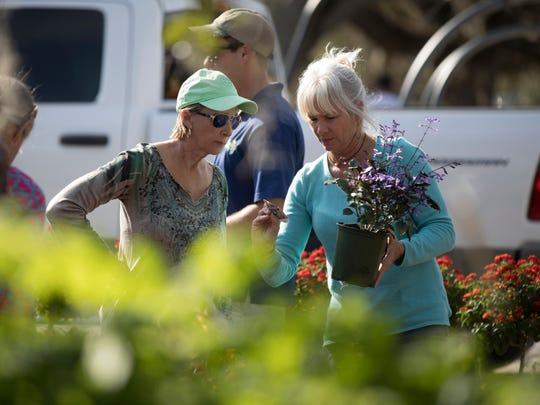 Gina Hodges (left) and Cindy Brister, both of Vero Beach, look at butterfly garden plants while attending the first day of Gardenfest! at Riverside Park in Vero Beach Feb. 3, 2018. The 17-year-old event is organized by the Garden Club of Indian River County