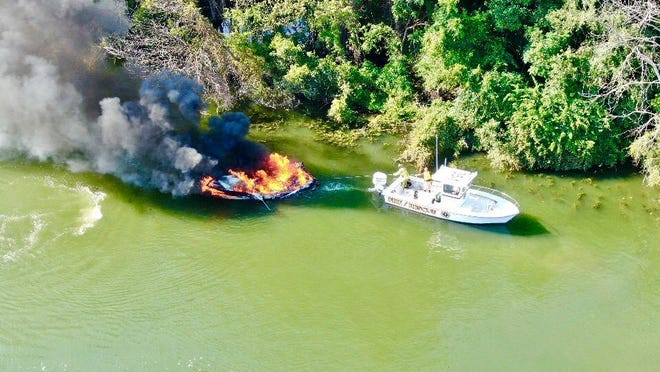 Members of the Monroe Township Volunteer Fire Department tow a burning vessel to safety Sunday in Bolles Harbor.