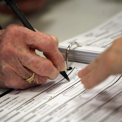 A voter signs a poll book before voting.