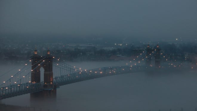 Fog hugs the Ohio River as it passes under the Roebling Suspension Bridge on Tuesday evening.