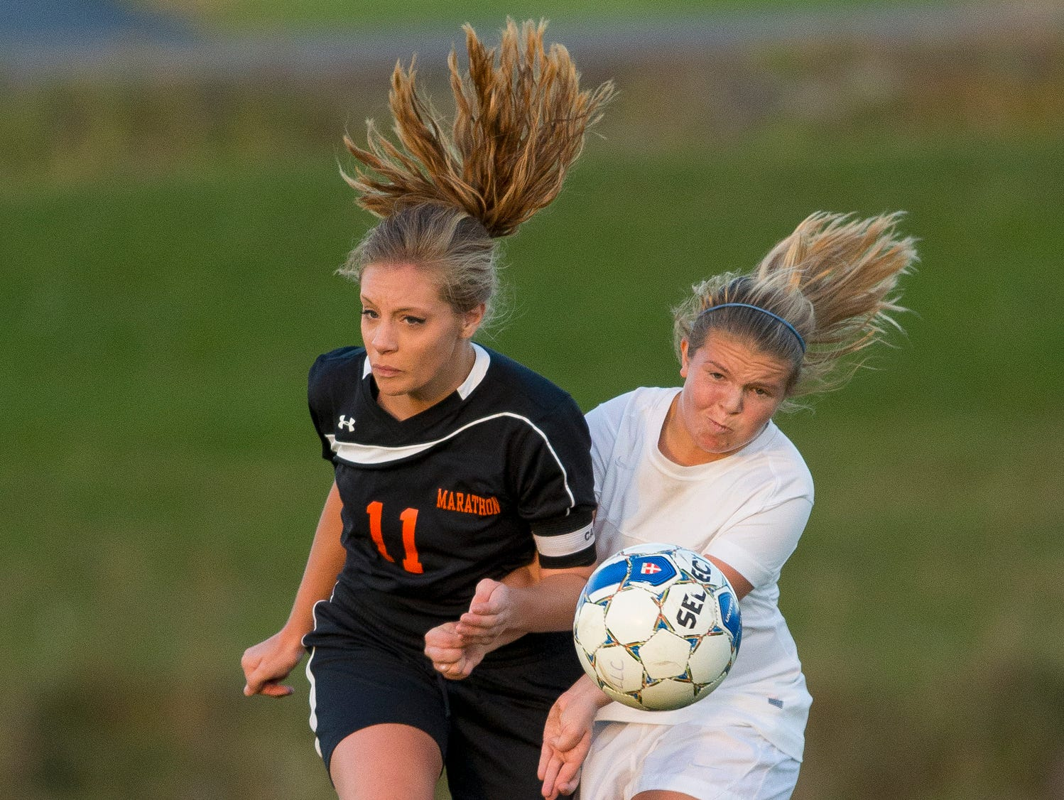 Marathon's Stephanie Wales, left, and Lansing's Reilly Zajac work to control the ball during the first half of their Section 4 Class C semifinal Tuesday evening in Lansing. The host Bobcats won, 5-1, and will play Elmira Notre Dame on Friday in Norwich for the sectional championship.