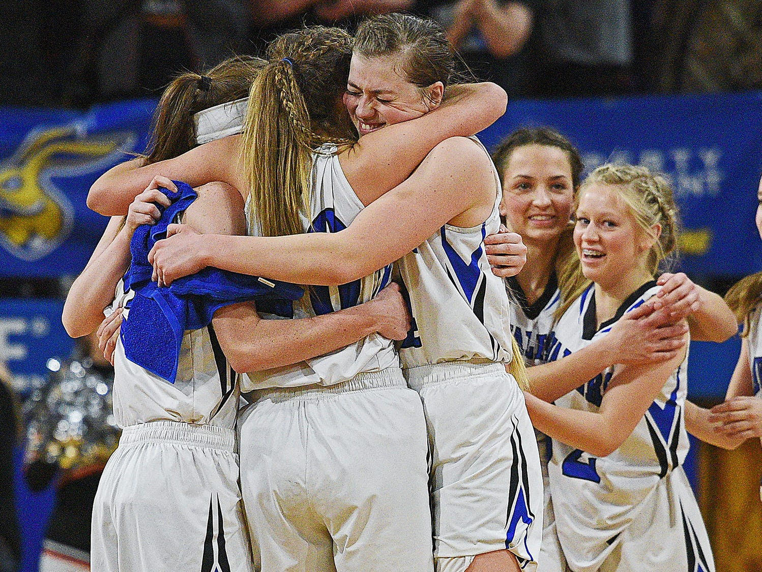 St. Thomas More's Jayden Bies (3), Klaire Kirsch (20) and Aislinn Duffy (44) hug while celebrating their 47-36 win over Lennox in the 2017 SDHSAA Class A State Girls Basketball Tournament championship game for their fourth consecutive title Saturday, March 11, 2017, at Frost Arena on the South Dakota State University campus in Brookings, S.D.