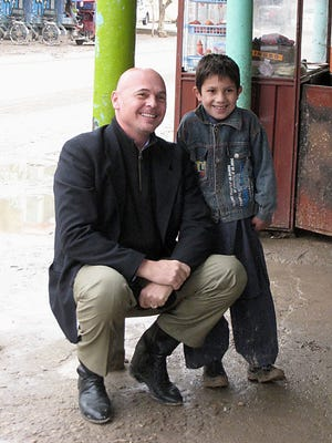Rod McSherry, New Mexico State University Gerald Thomas Chair for Global Agricultural Initiatives, is seen next to a boy while assigned to Afghanistan during his career as foreign service officer with the USDA.