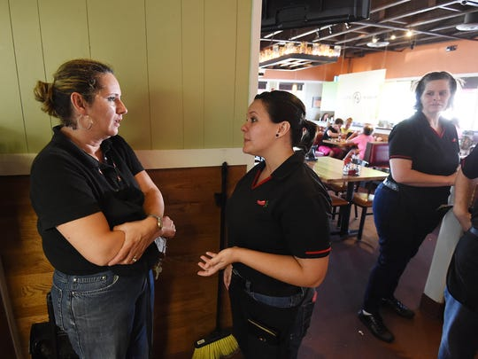 Sarah Reynolds, center, talks with a fellow employee at Chili's. Both Sarah and her partner, Nikki, work at the restaurant. Sarah said most co-workers know about her sexuality and are supportive, but she did have one encounter with an employee who called her a faggot.