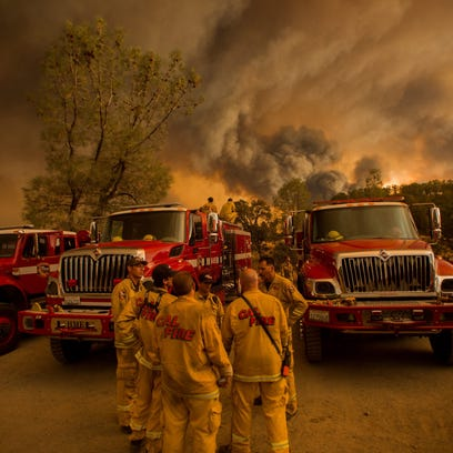 Firefighters confer as the Rocky Fire burns near Clearlake,