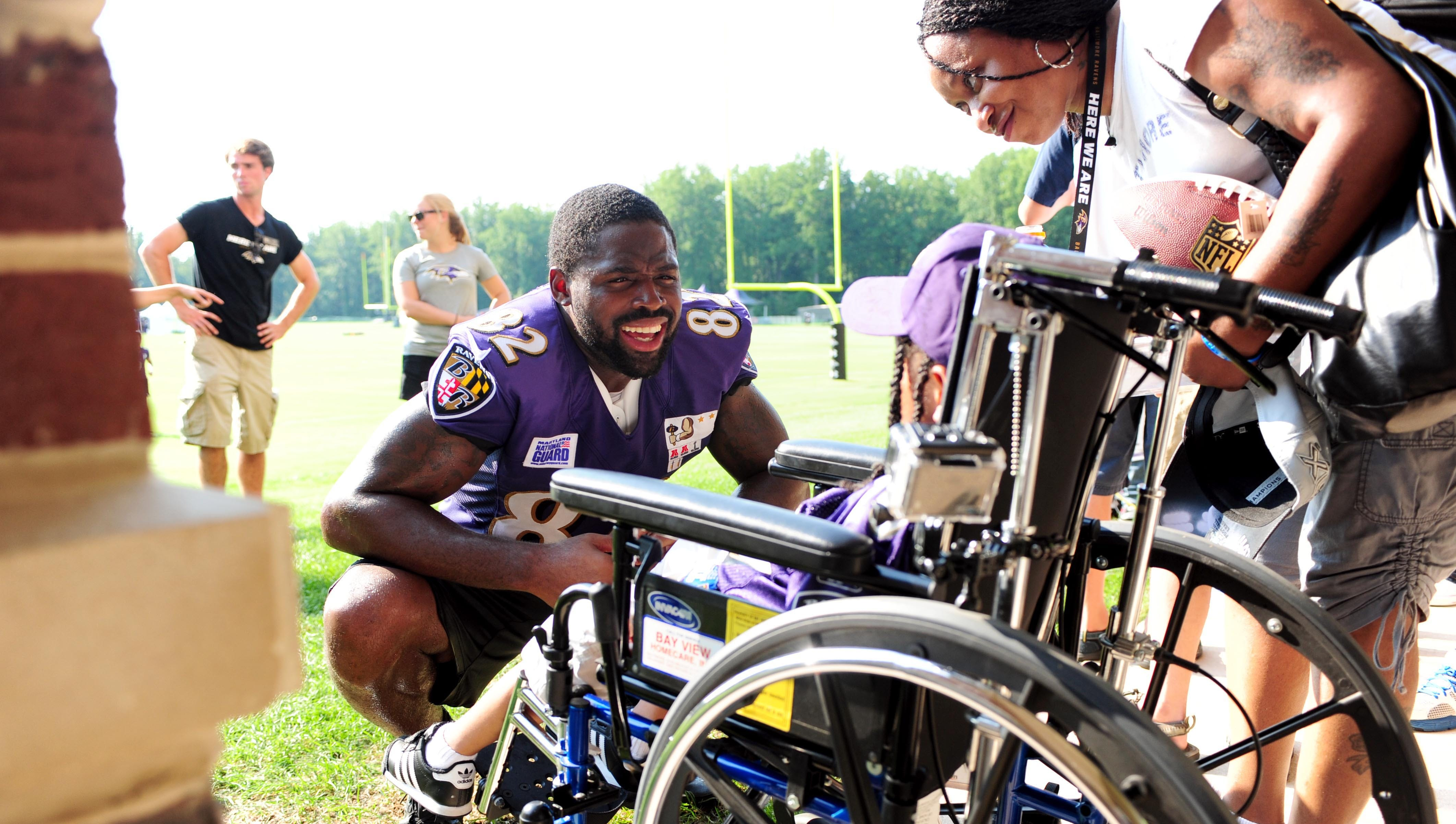 Baltimore Ravens wide receiver Torrey Smith signs autographs for a fan after training camp at the Under Armour Performance Center on Aug. 12.