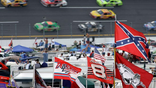 "FILE - In this Oct. 7, 2007, file photo, a Confederate flags fly in the infield as cars come out of turn one during a NASCAR auto race at Talladega Superspeedway in Talladega, Ala. NASCAR  backed South Carolina Gov. Nikki Haley's call this week to remove the Confederate flag from the Statehouse grounds in the wake of the Charleston church massacre. Though NASCAR now bars the use of the flag in any ""official capacity,"" they are as easy to find at NASCAR races as cutoff jeans, cowboy hats, and beer."