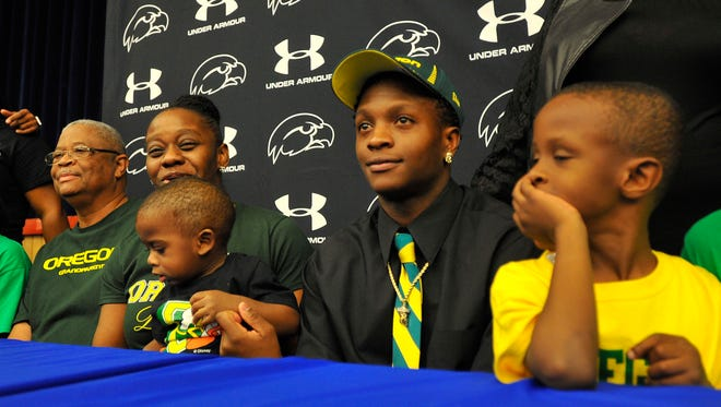 Oregon football recruit Darrian McNeal, center, sits for a photo with his mother, Deonzia Woullard, left, holding her 1-year-old son, Clarence Gordon, and his brother Dyson McNeal, 5, Wednesday at Armwood High School in Seffner, Fla.