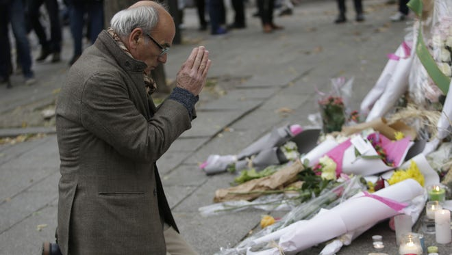A man pays his respects at a pop-up memorial to the victims of an attack, along a rail cordon close to the Bataclan theater in Paris, on Nov. 14.