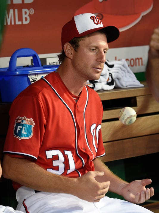 Washington Nationals pitcher Max Scherzer (31) juggles a ball in the dugout during an interleague exhibition baseball game against the Minnesota Twins, Friday, April 1, 2016, in Washington. The Nationals won 4-3. (AP Photo/Nick Wass)