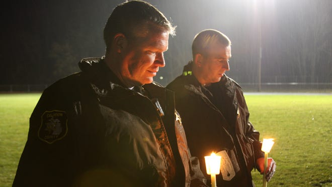 Calhoun County Sheriff Department Deputy Mark Elferdink, right, and Lt. Aaron Wiersma, were among the hundreds of people who attended a vigil honoring Kaleigh Woodman and Sabrina Almaraz at Pennfield High School's football field in December. Elferdink shot his wife and himself in a murder suicide at their McAllister Road home.