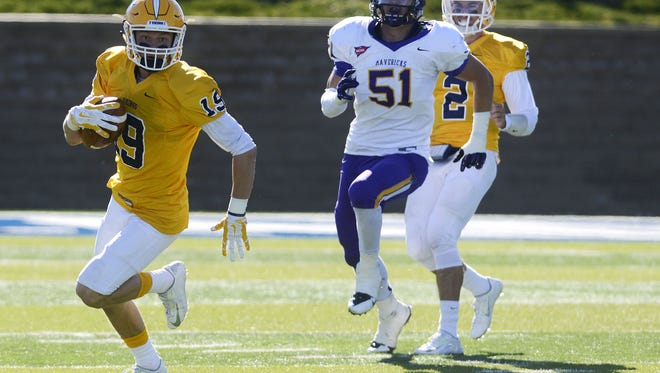 Augie's Matt Heller carries the ball with Minnesota State's Colt Nero trailing behind in Saturday's game at Kirkeby-Over Stadium, Oct 25, 2014.
