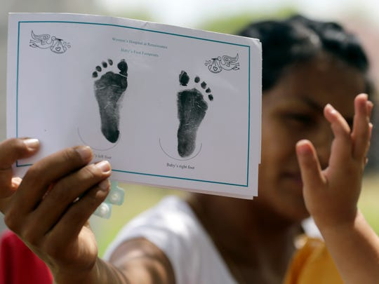 In this Sept. 16, 2015, photo, a woman in Sullivan City, Texas, who said she entered the country illegally shows the footprints of her daughter, reaching into photo, who was born in the United States, but was denied a birth certificate. Texas has for seven years said it won't accept Mexican identification cards when issuing birth certificates for children of people in the United States illegally. But it doesn't appear to have stepped up enforcement until recently, amid mounting political pressure to get tougher on immigration, documents obtained by The Associated Press show.