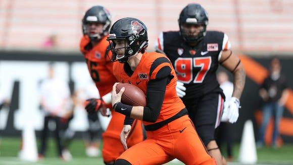 Oregon State quarterback Jake Luton carries the ball