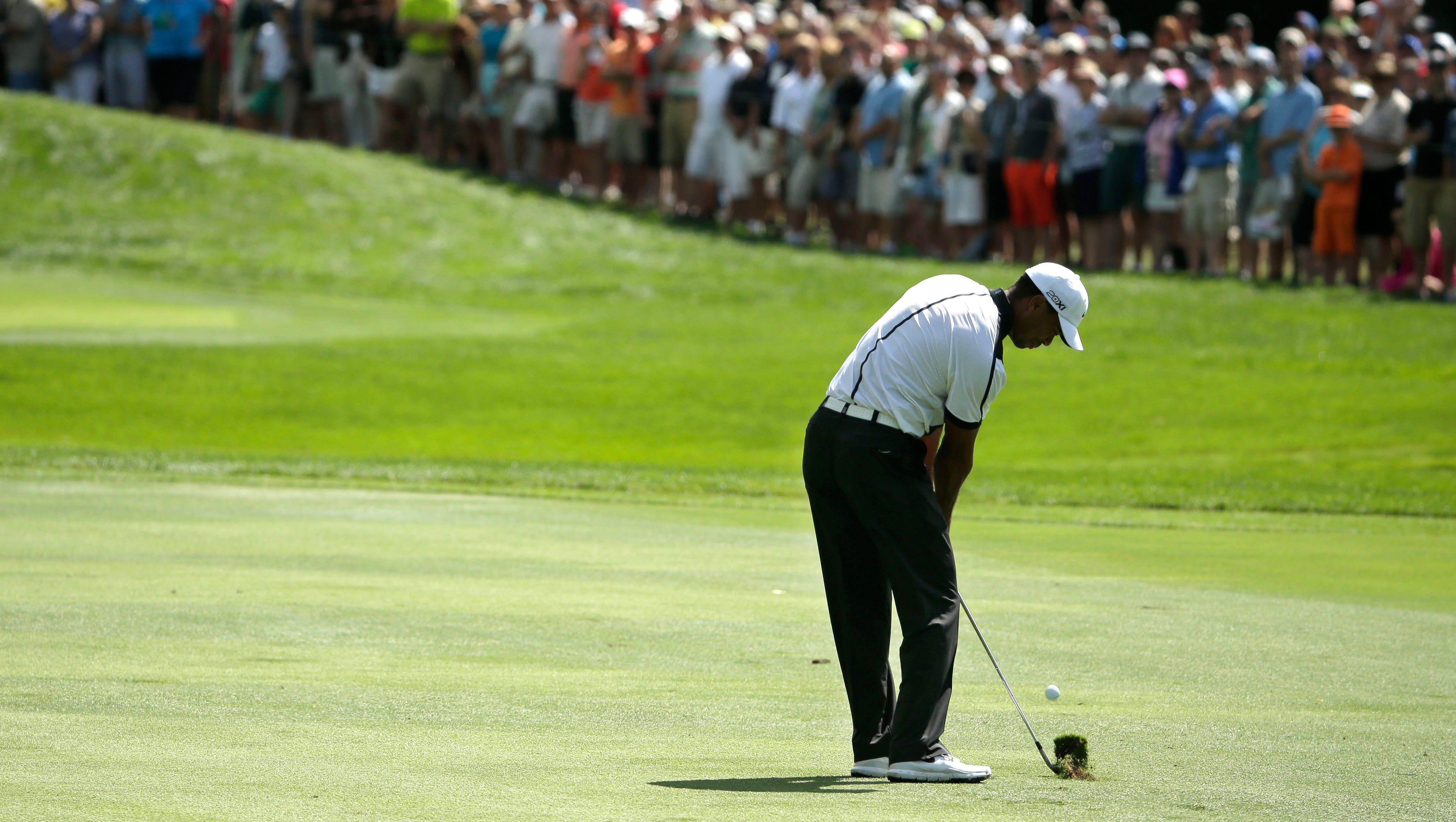 Tiger Woods hits from the fairway on the first hole.