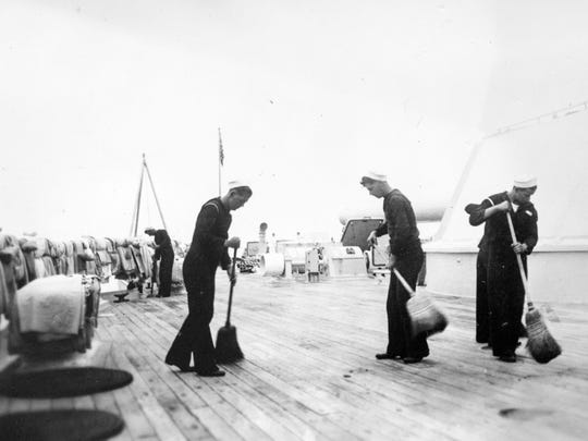 Crew members sweep the deck of the USS Arizona. The Arizona's decks were made from teakwood and had to be meticulously maintained to protect from damage from the sea water and weather.
