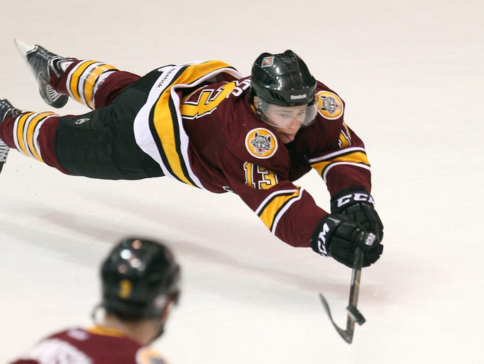 Chicago's Michael Davies (13) dives to keep the puck in the Amerks' zone during Game 1 of their playoff series April 25, 2014, in Rochester. The Wolves won Game 1, 4-3, in overtime.