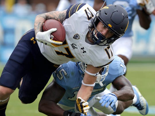 California's Vic Wharton III (17) runs the ball as North Carolina's Donnie Miles (15) reaches in for the tackle during the first half of an NCAA college football game in Chapel Hill, N.C., Saturday, Sept. 2, 2017. California won 35-30.(AP Photo/Gerry Broome)