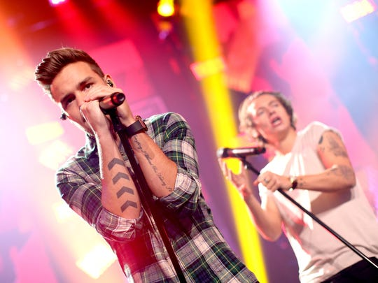 """Musicians Liam Payne (L) and Harry Styles perform onstage at the """"One Direction iHeartRadio Album Release Party"""" hosted by Ryan Seacrest at the iHeartRadio Theater Los Angeles"""