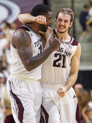 Texas A&M Aggies forward Kourtney Roberson (14) and guard Alex Caruso (21) celebrate after the Aggies defeated the Florida Gators 63-62 at Reed Arena.