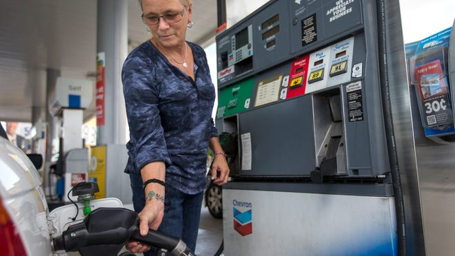 Kim Early tops off her gas tank at the Chevron station at 44th Street and McDowell Road in Phoenix, on Friday, September 26, 2014. State gasoline taxes imposed by Arizona are among the lowest in the nation, making it worthwhile to fill up your tank before crossing over to California. A study of state gasoline taxes found that Arizona's 18 cents a gallon is tied for 36th place among the states and Washington, D.C.