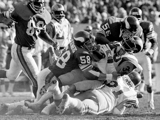 FILE - In this Dec. 26, 1976, file photo, Los Angeles Rams L. McCutcheon (30) is stopped by Minnesota Vikings Wally Hilgenberg (58) and Amos Martin (55) after gaining ten in the first quarter of the NFC championship game at Bloomington, Minn. Nearly a decade after Hilgenberg's death, his widow can still hear his voice telling her he loves her, at the push of a button. It's programmed into a stuffed bear he gave her shortly before succumbing to ALS in 2008. (AP Photo/File)