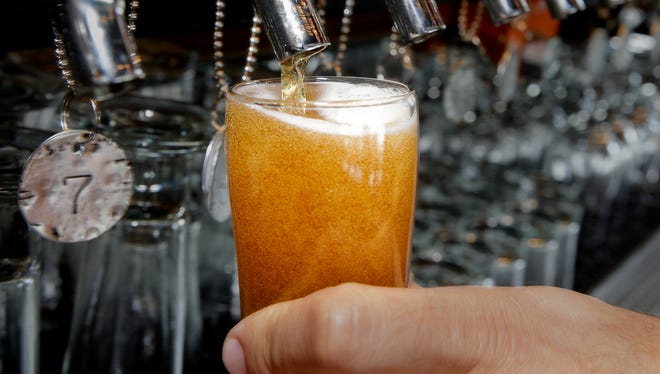 A bartender pours a beer.
