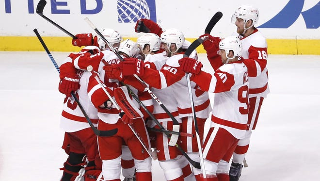 The Detroit Red Wings celebrate their 3-2 win over the Chicago Blackhawks after a shootout period of an NHL hockey game Wednesday, Feb. 18, 2015, in Chicago.