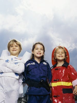(From left) Kids dressed up as an astronaut, police officer and firefighter.