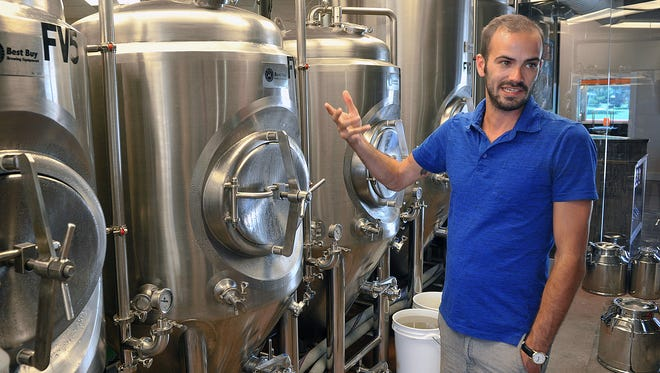 Daniel Anderson, co-owner of Sidecar Brewing, talks about the fermentation process at his brewery located in the former Pumpjack Diner building on Broad Street.