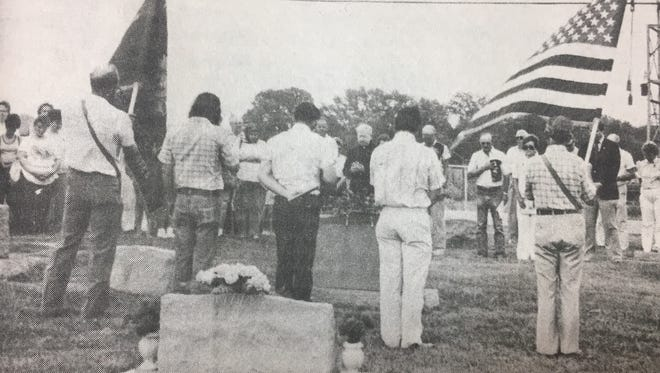 Father Hank Frantz, center, lead a prayer as several Uniontown residents observed Memorial Day services at St. Agnes Cemetery in May 1987.